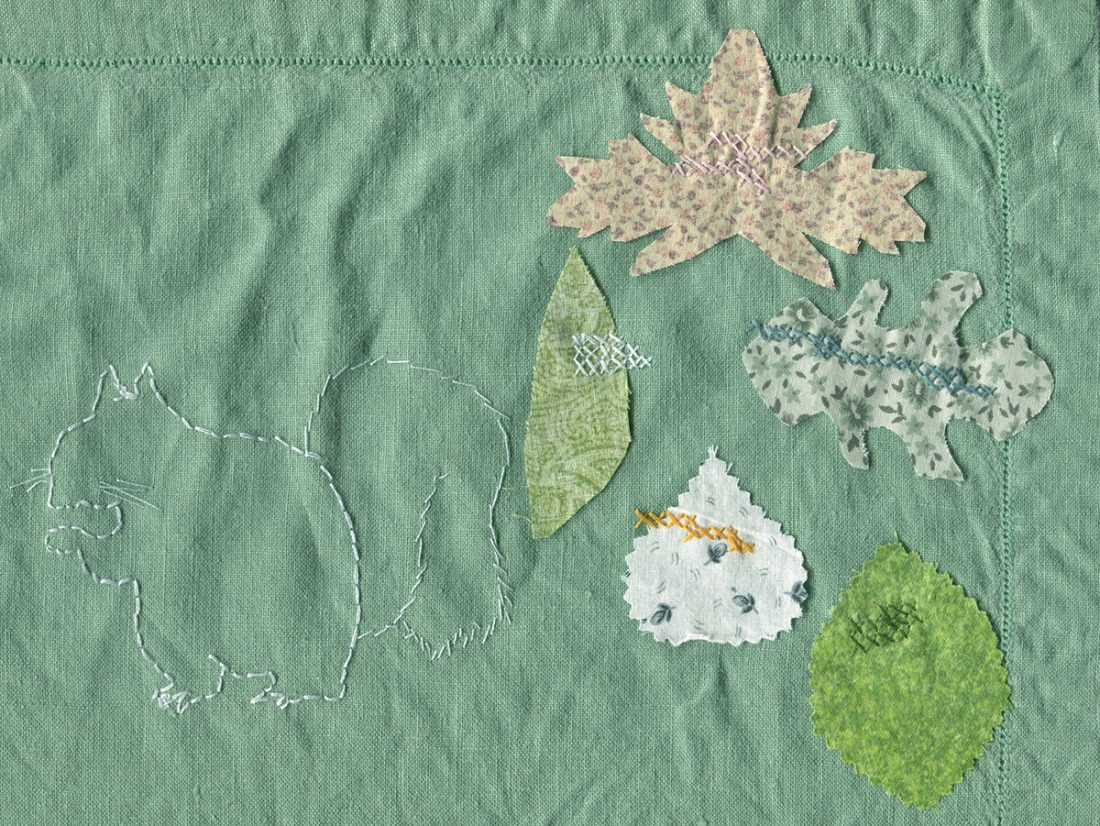 Green linen embroidered with the white outline of a squirrel, and five leaf shapes cut from multiple colors of fabric secured to the linen with cross stitches in various colors.