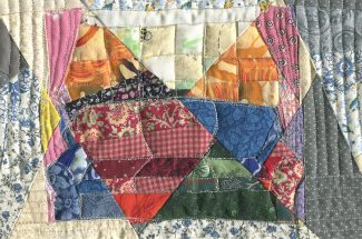 A couch in front of a window, but it is pieced from multiple fabrics and quilted. It is fragmented and multicolored.
